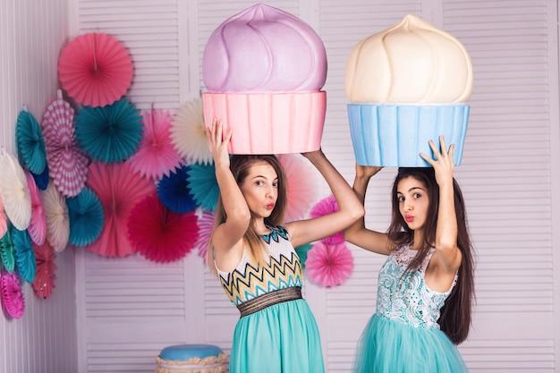 Deux belles filles en robes bleues tiennent dans leurs mains d'énormes gâteaux en studio avec un décor de macarons.
