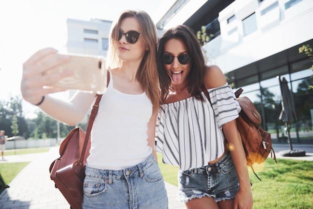 Deux belles filles avec des sacs à dos marchent ensemble dans la ville. des amis assez mignons partagent des secrets.