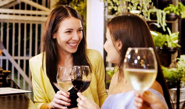 Deux belles filles sonnant des verres avec des boissons au bar
