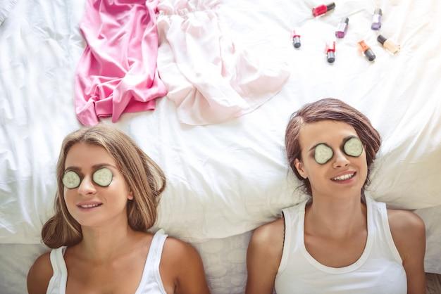 Deux belles filles sourient en position couchée avec des concombres.
