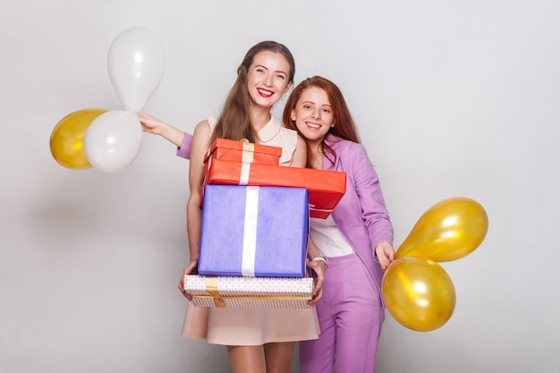 Deux belles filles tenant une boîte à cadeaux et une montgolfière ont un air de bonheur et montrent un signe av à la caméra. prise de vue en studio