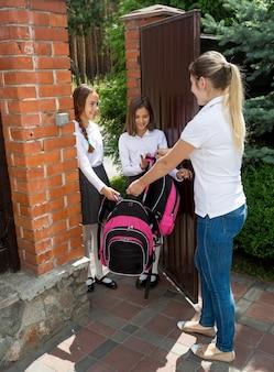 Deux belles filles vont à l'école et disent au revoir à leur mère