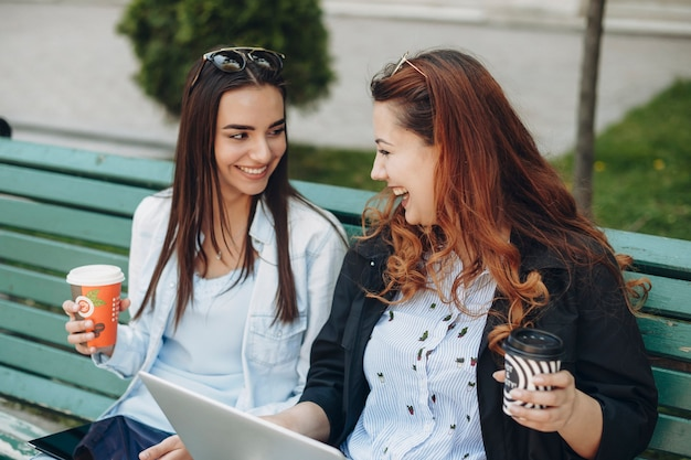 Deux belles jeunes copines buvant du café assis sur un banc à l'aide d'un ordinateur portable et d'une tablette se regardant en riant avec une tasse de café chaud.