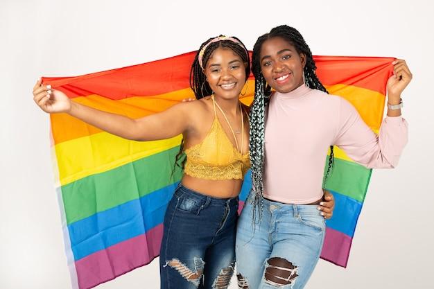 Deux belles jeunes femmes africaines avec drapeau lgbt sur fond blanc