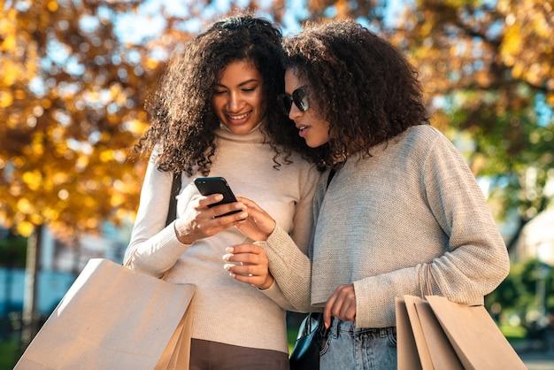 Deux belles jeunes femmes africaines élégantes marchant ensemble dans la rue, utilisant un téléphone portable, parlant, portant des sacs à provisions