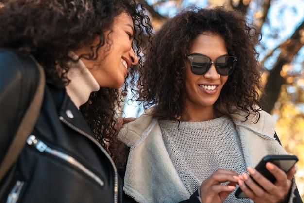 Deux belles jeunes femmes africaines élégantes marchant ensemble dans la rue, utilisant un téléphone portable, parlant