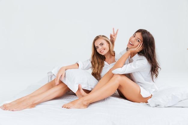 Deux belles jeunes femmes assises sur un lit blanc et montrant un geste de victoire