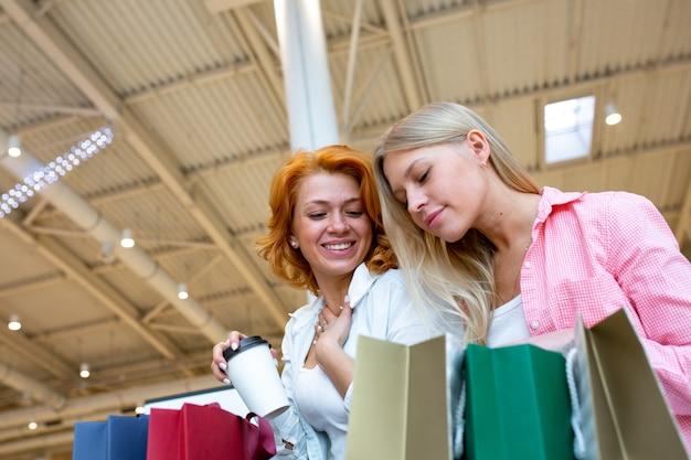 Deux belles jeunes femmes dans un centre commercial vérifiant les sacs