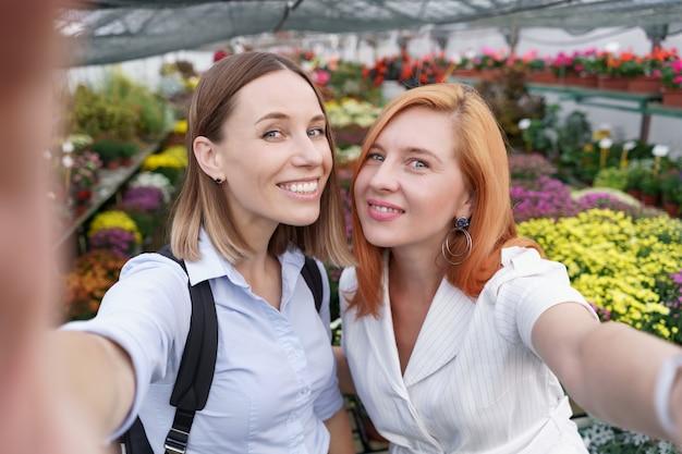 Deux belles jeunes femmes faisant selfie sur fond de fleurs dans la serre