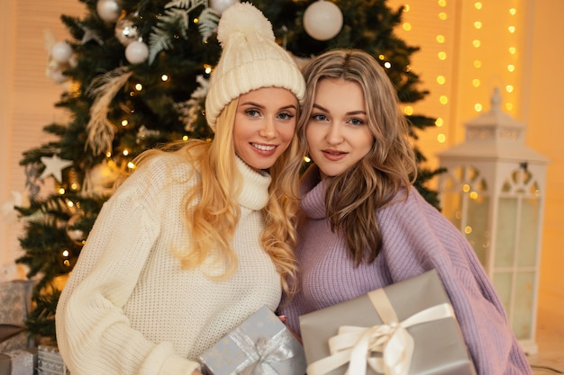 Deux belles jeunes femmes heureuses avec le sourire dans un pull tricoté à la mode et un chapeau vintage tiennent des cadeaux et sont assises près d'un arbre de noël avec des lumières. vacances d'hiver