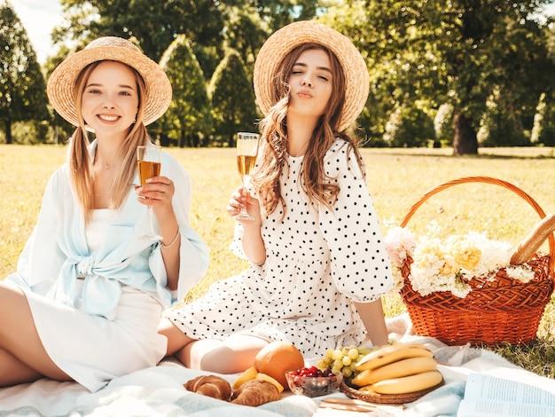 Deux belles jeunes femmes hipster souriantes en robe d'été et chapeaux. femmes insouciantes faisant un pique-nique à l'extérieur.