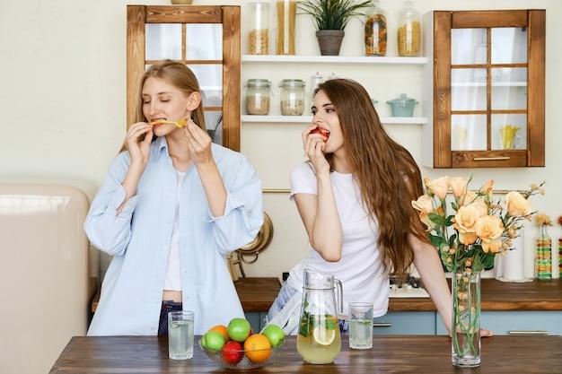 Deux belles jeunes femmes mangent des fruits dans la cuisine