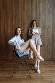 Deux belles jeunes femmes modèles posant en studio dans une nouvelle collection de vêtements d'été