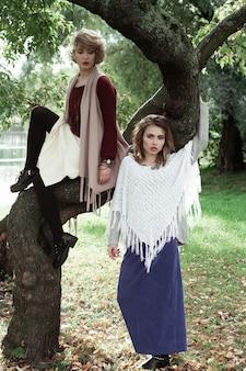 Deux belles jeunes femmes posant sur un arbre, parc automne