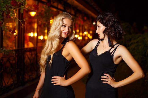 Deux belles jeunes femmes posant devant la caméra à la lumière de la ville de nuit