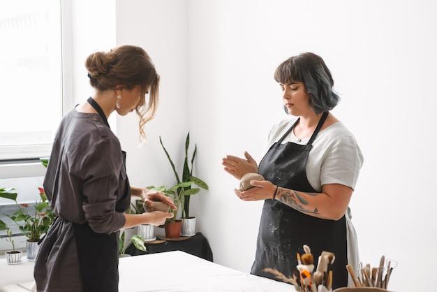 Deux belles jeunes femmes potier créant des plats