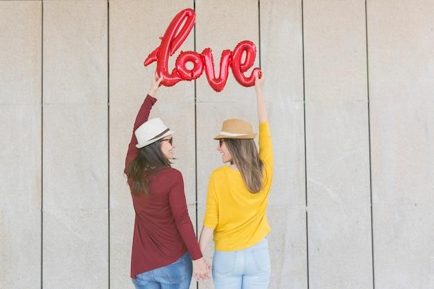 Deux belles jeunes femmes s'amusant à l'extérieur avec un ballon rouge avec une forme de mot d'amour. vêtements décontractés. ils portent des chapeaux et des lunettes de soleil modernes. lifestyle extérieur