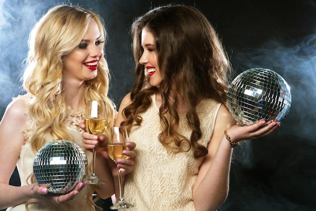 Deux belles jeunes femmes avec des verres à vin