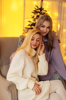 Deux belles jeunes femmes vêtues d'un pull vintage à la mode sont assises dans un fauteuil près de l'arbre de noël à la maison. vacances d'hiver et vacances