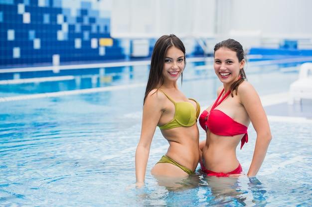 Deux belles jeunes filles brunes dans la piscine à l'intérieur