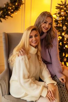 Deux belles jeunes filles heureuses avec un sourire dans un pull en tricot sont assises sur une chaise près de l'arbre de noël et des lumières jaunes à la maison