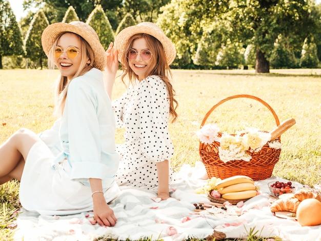 Deux belles jeunes filles hipster souriantes en robe d'été et chapeaux à la mode. femmes insouciantes faisant un pique-nique à l'extérieur.