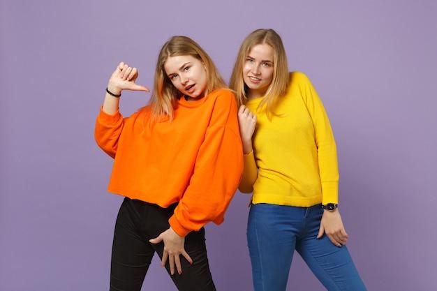 Deux belles jeunes filles jumelles blondes dans des vêtements colorés vifs pointant le pouce sur elle-même isolée sur un mur bleu violet pastel. concept de mode de vie familial de personnes. .