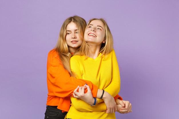 Deux belles jeunes filles jumelles blondes vêtues de vêtements colorés vifs se serrant dans leurs bras, regardant de côté isolées sur un mur bleu violet pastel. concept de mode de vie familial de personnes.
