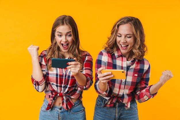 Deux belles jeunes filles portant des chemises à carreaux s'amusant et jouant à des jeux vidéo sur des téléphones portables isolés