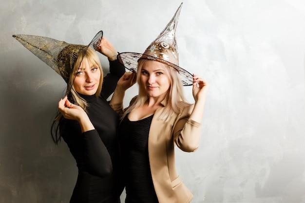 Deux belles jeunes filles vêtues d'une robe noire de sorcière