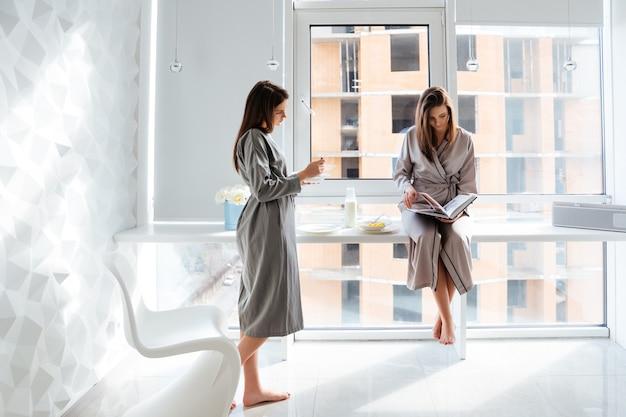 Deux belles jeunes soeurs paisibles jumelles lisant un livre et prenant le petit déjeuner à la maison