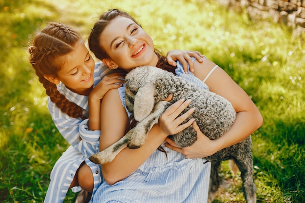 Deux belles et mignonnes filles en robes bleues avec de belles coiffures et de maquillage assis