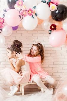Deux belles petites filles avec des couronnes sous un ballon d'anniversaire et des décorations en arc de fleurs en papier. photozone enfantine pour la fête