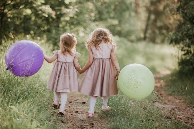 Deux belles petites filles en été dans un parc avec des ballons à la main.