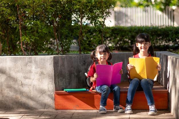 Deux belles petites filles lisant des livres dans le jardin. le concept d'éducation