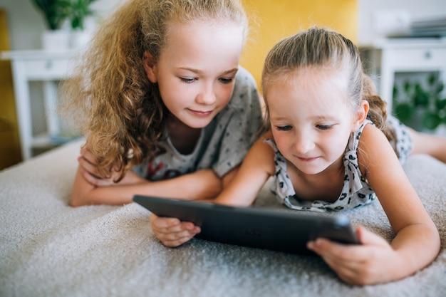 Deux belles petites sœurs allongées dans le lit et regardant l'écran d'une tablette, des enfants intelligents utilisant une technologie intelligente