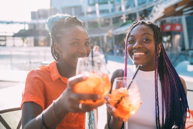 Deux belles sœurs de femmes noires assis bar faisant un toast en souriant