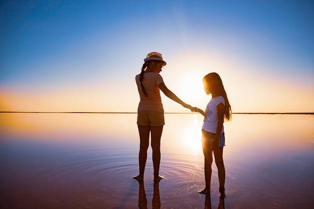 Deux belles sœurs heureuses marchent le long du lac salé miroir