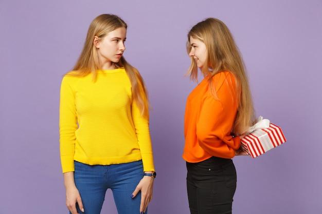 Deux belles sœurs jumelles blondes vêtues de vêtements vifs tiennent une boîte cadeau à rayures rouges avec un ruban cadeau isolé sur un mur bleu violet. anniversaire de la famille des gens, concept de vacances.
