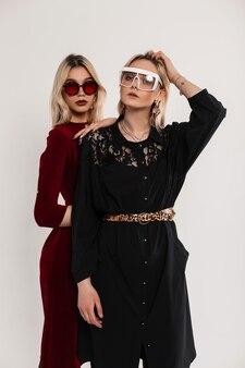 Deux belles soeurs jumelles à la mode avec des lunettes de soleil dans une élégante robe vintage à la mode près du mur gris