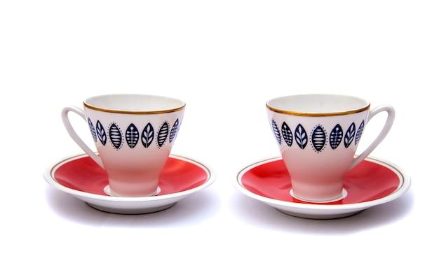 Deux belles tasses de café rouge avec des motifs de soucoupes, isoler sur fond blanc