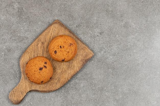 Deux biscuits au chocolat sur planche de bois.