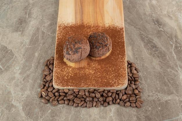 Deux biscuits au chocolat sur une plaque en bois avec des grains de café