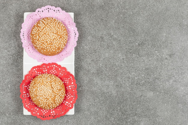 Deux biscuits aux graines de sésame sur soucoupe blanche