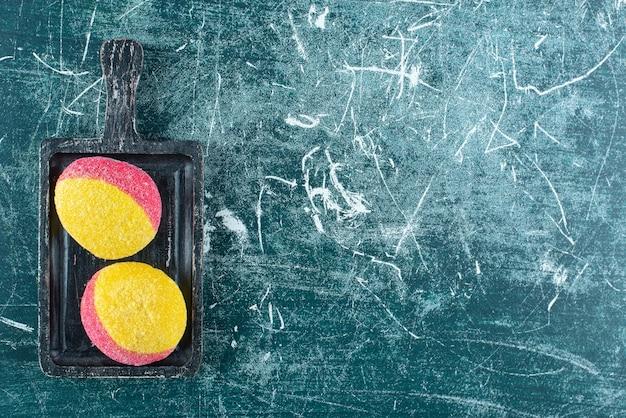 Deux biscuits colorés sur une planche à découper noire.