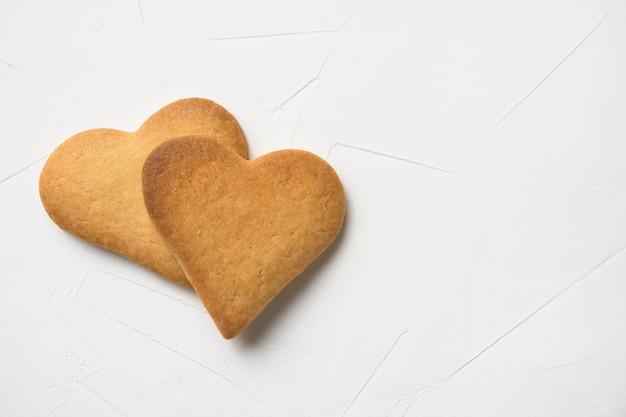 Deux biscuits en forme de coeur faits maison sur blanc