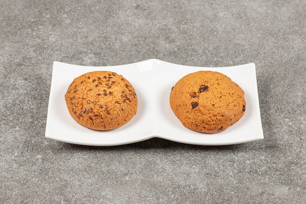 Deux biscuits frais faits maison sur plaque blanche.