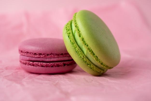 Deux biscuits macaron français verts et violets se trouvent sur un fond de papier rose. vue de côté