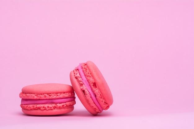 Deux biscuits macaron rose sur fond rose.