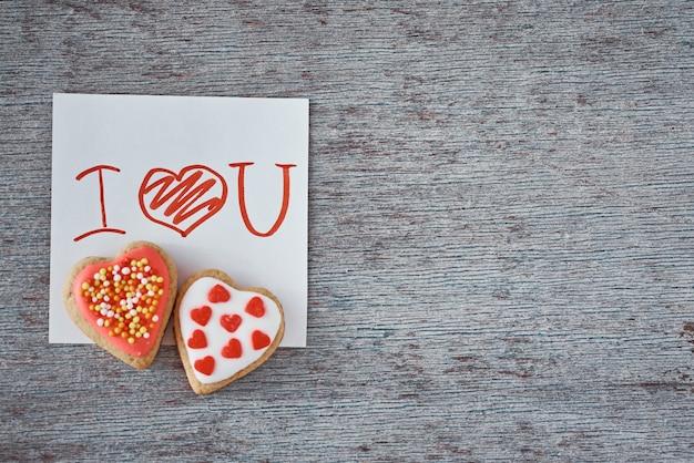 Deux biscuits en pain d'épice en forme de cœur et je t'aime note